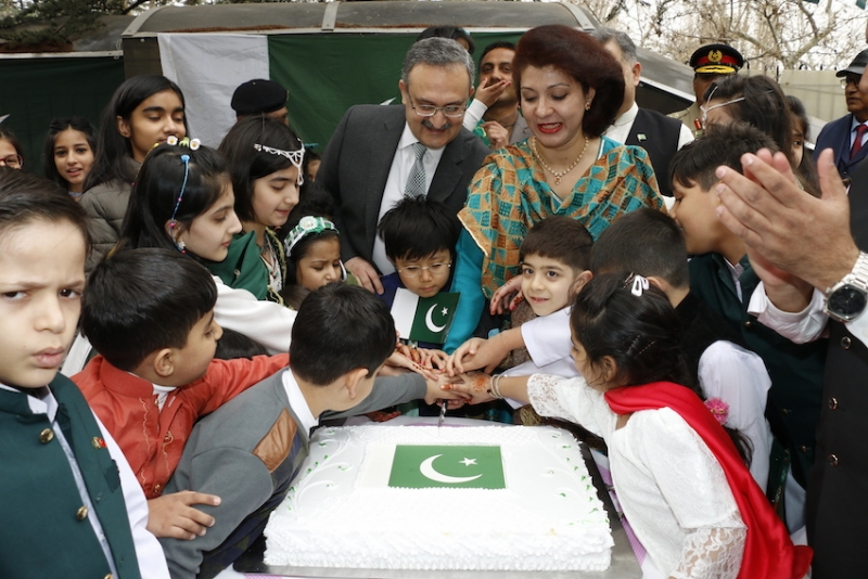Flanked by Pakistani children, Ambassador Syrus Sajjad Qazi and his spouse cutting cake to mark Pakistan Day