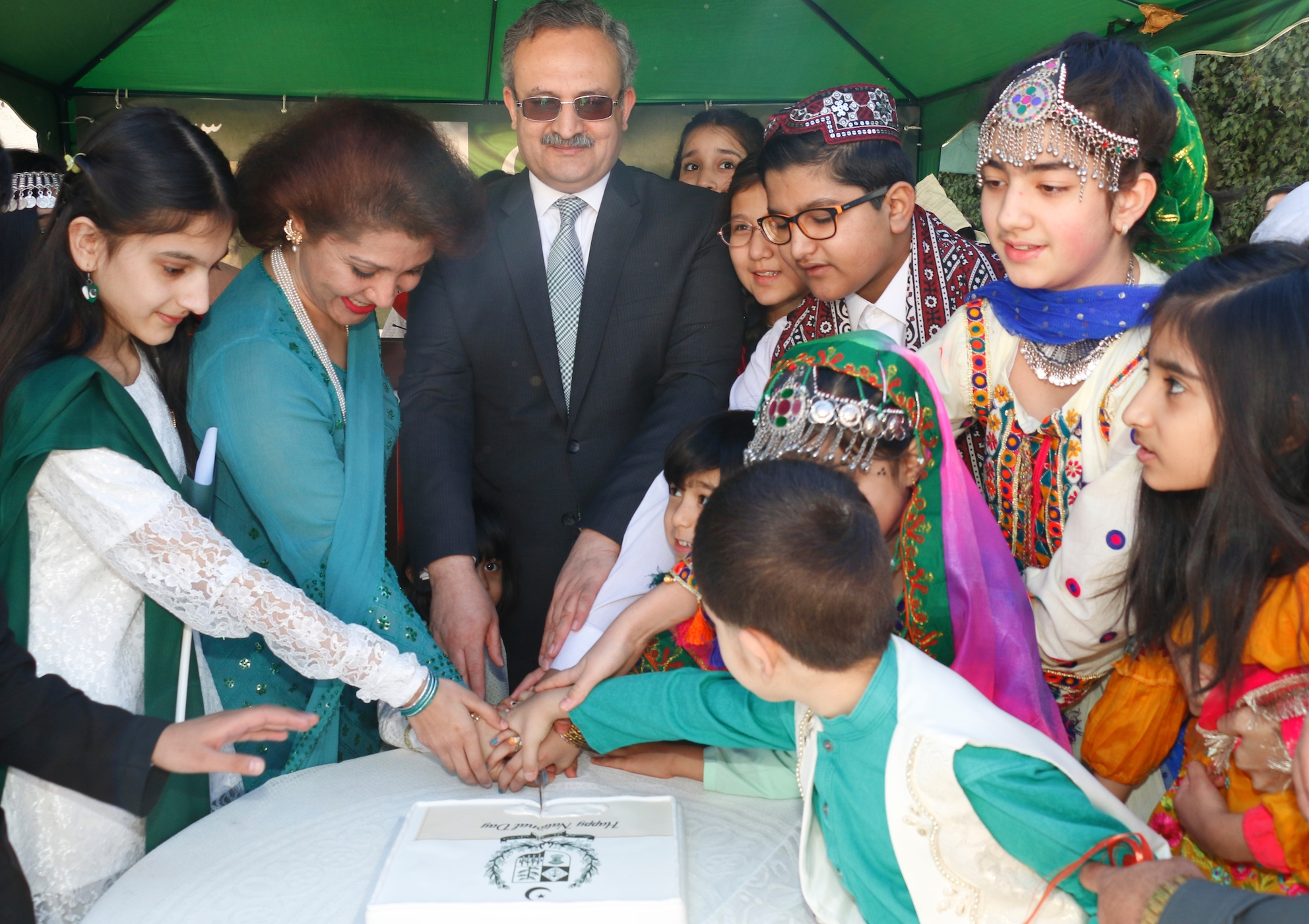 Flanked by Pakistani children, Ambassador Syrus Sajjad Qazi and his spouse cutting cake to mark Pakistan Day 23 March 2019